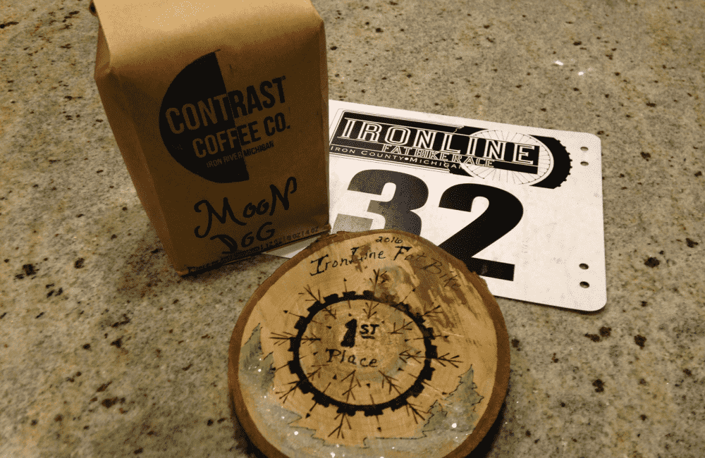 Ironline first place medallion, a bag of Contrast Coffee Co coffee beans, and an Ironline race number plate