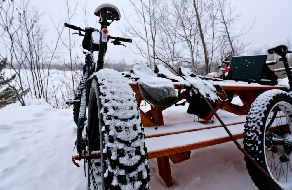Fat bikes leaning against a picnic table covered in snow
