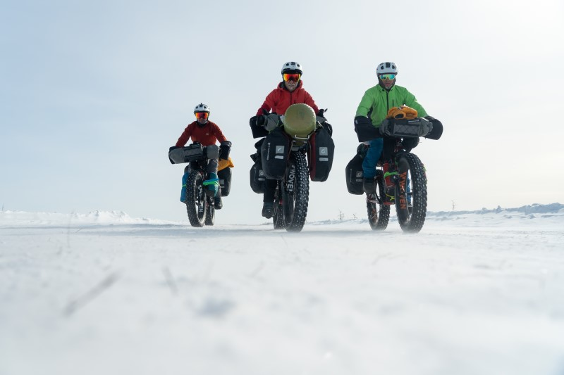Three riders riding on a snow covered trail on fat bikes loaded with equipment