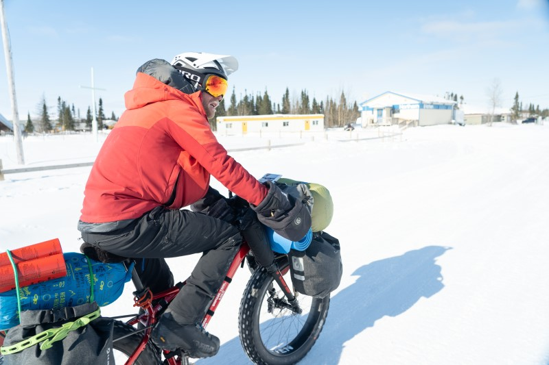 Rider on fat bike loaded with gear on a snow covered road