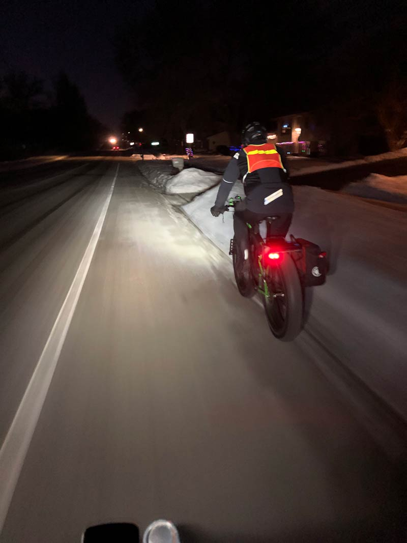 Fat bike rider in bike lane with tail light and high-vis vest in the early morning darkness