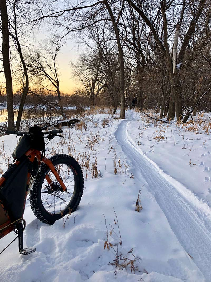 Fat bike parked along snowy tree-lined trail at sunrise