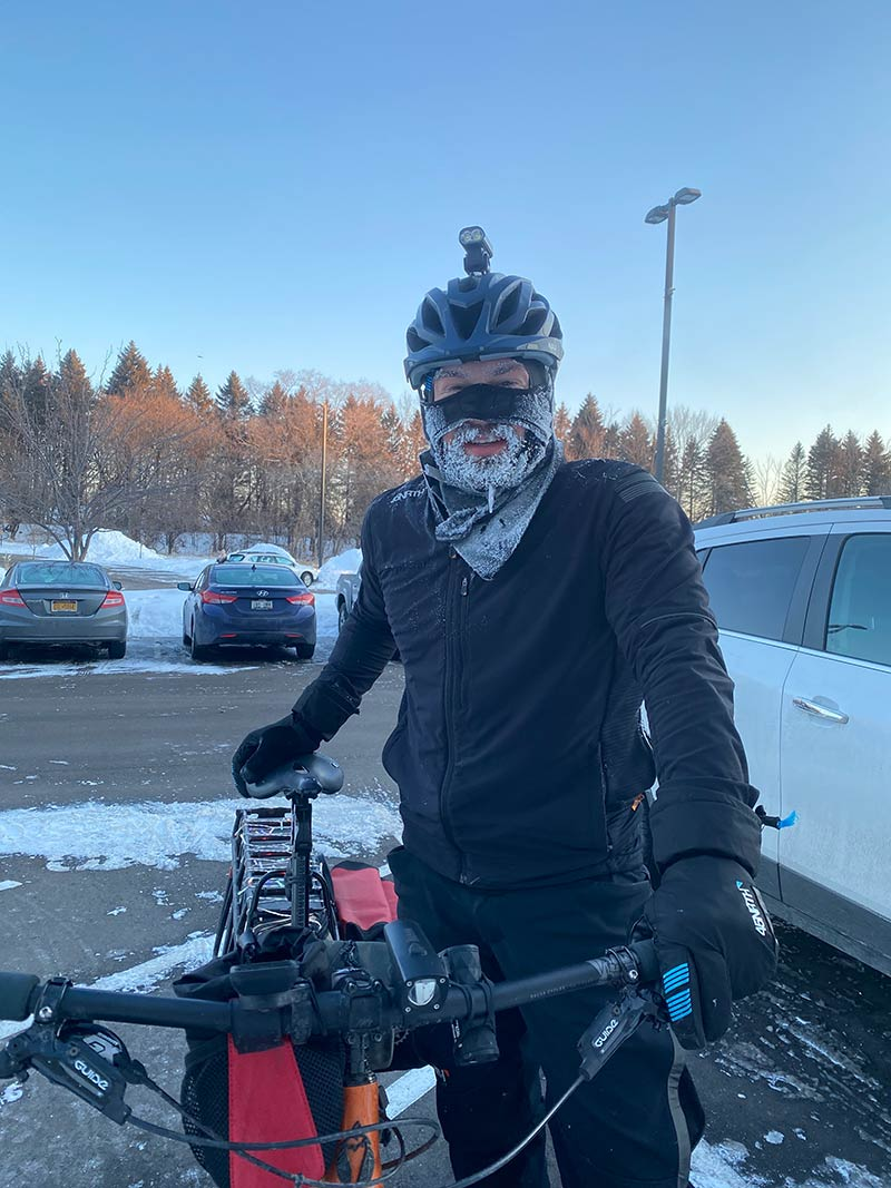 Fat bike rider in winter cycling gear standing next to bike with an ice-covered beard