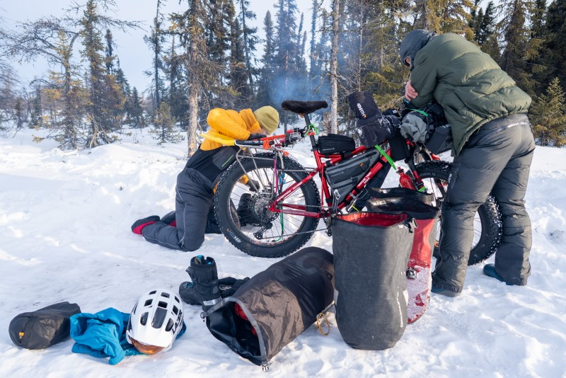 Two riders huddled around fat bike making repairs. Camping equipment and cycling gear scattered around the bike.