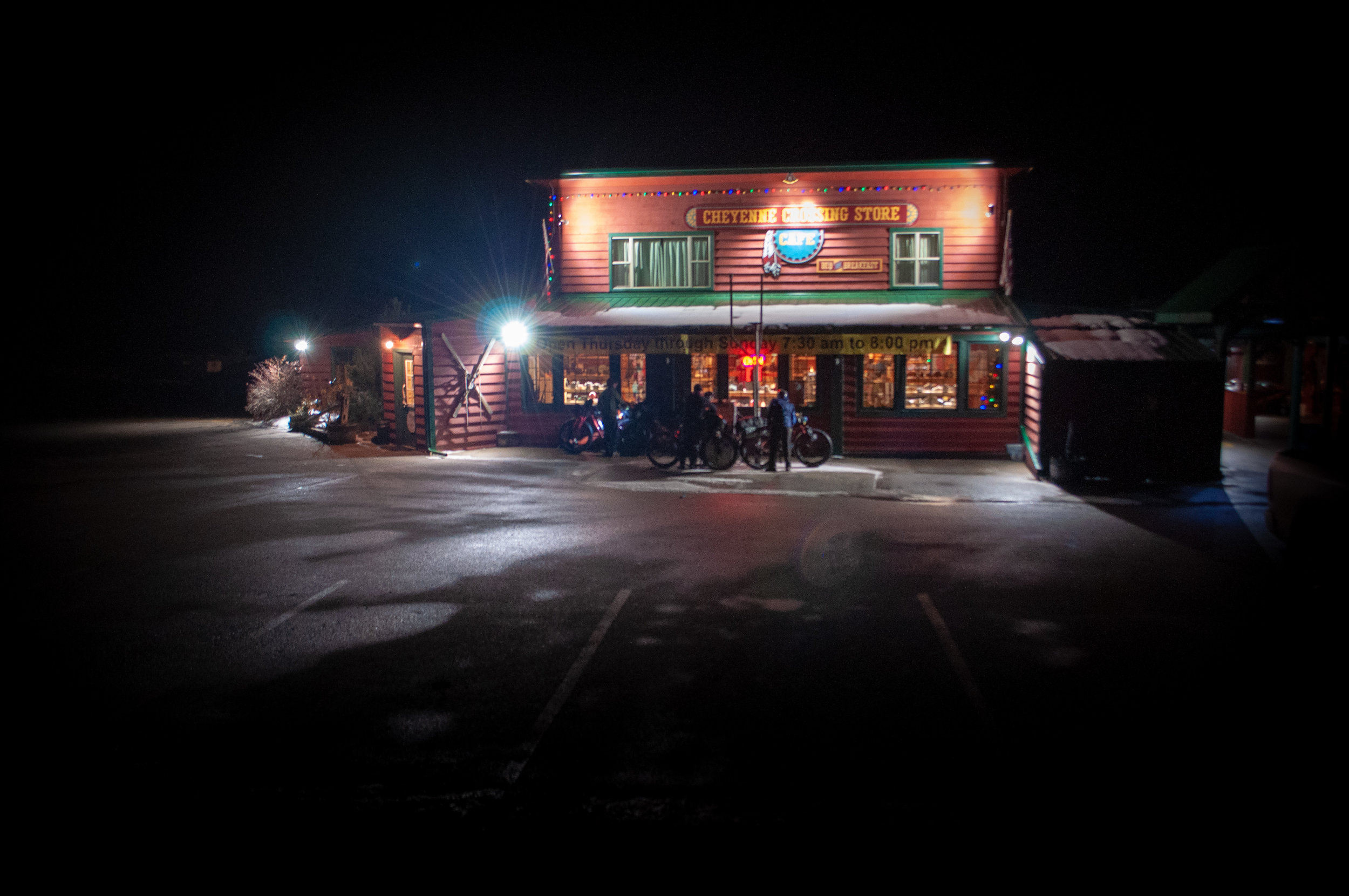 A group of fat bike riders standing in front of a small general store in the dark