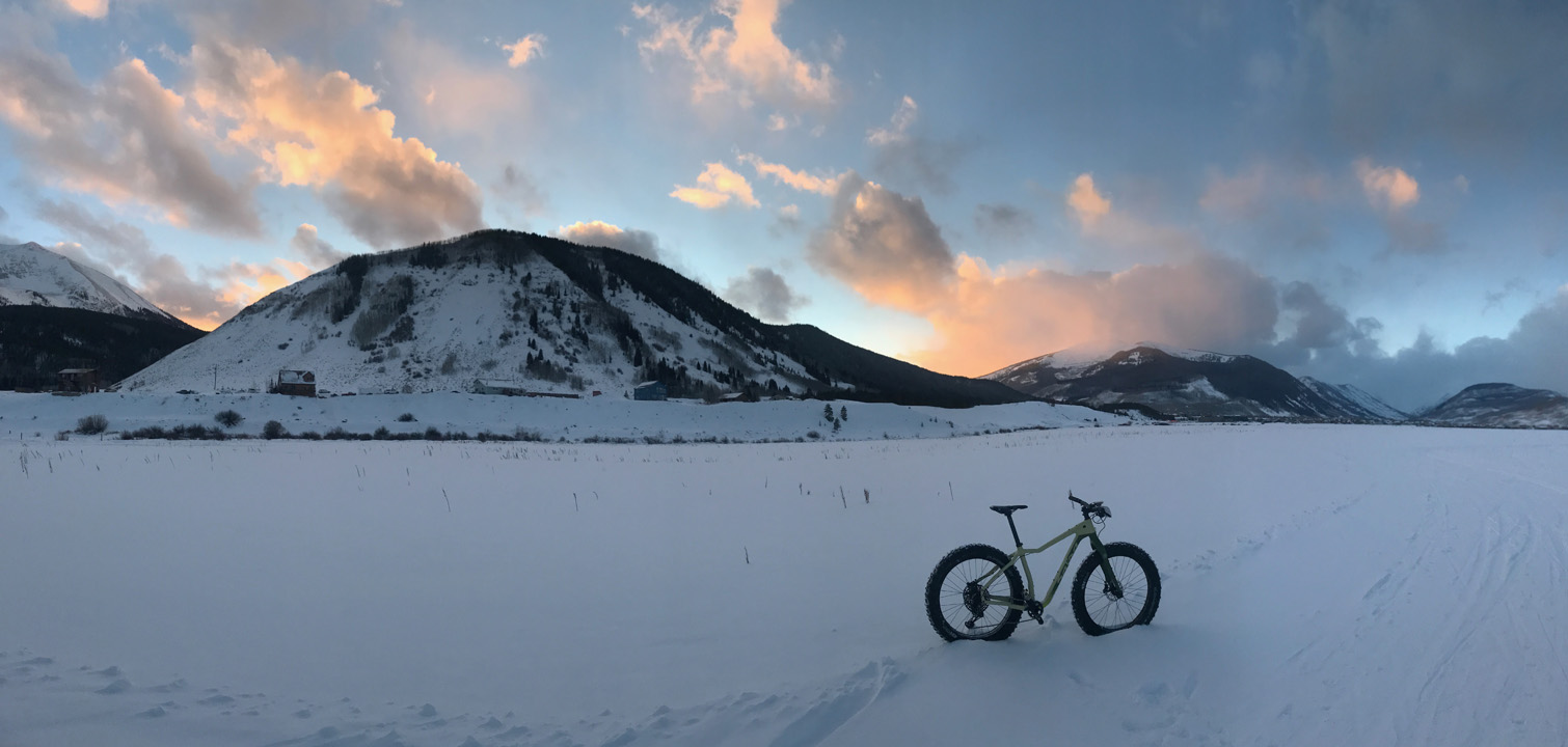 Upright fat bike in the snow with mountains in the background