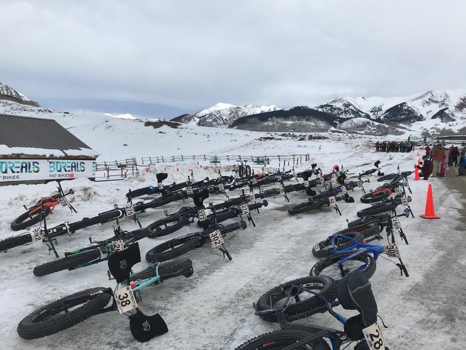 Dozens of fat bikes laid on the ground at the start of the course