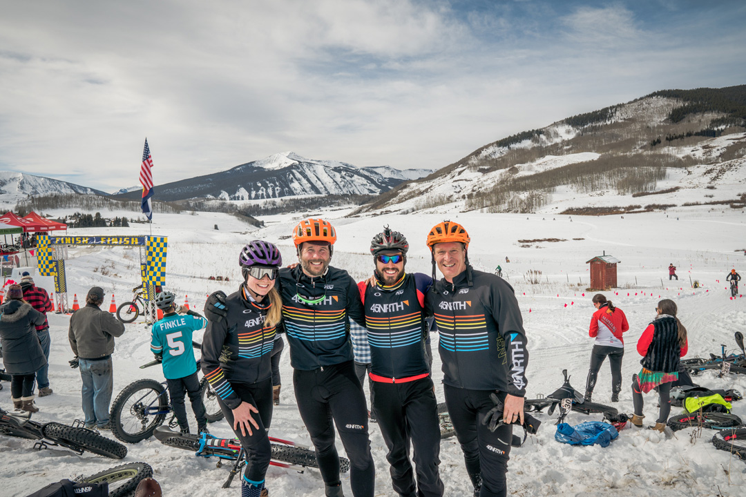 Four 45NRTH fat bike riders posing in front of the course finish line with mountains in the background