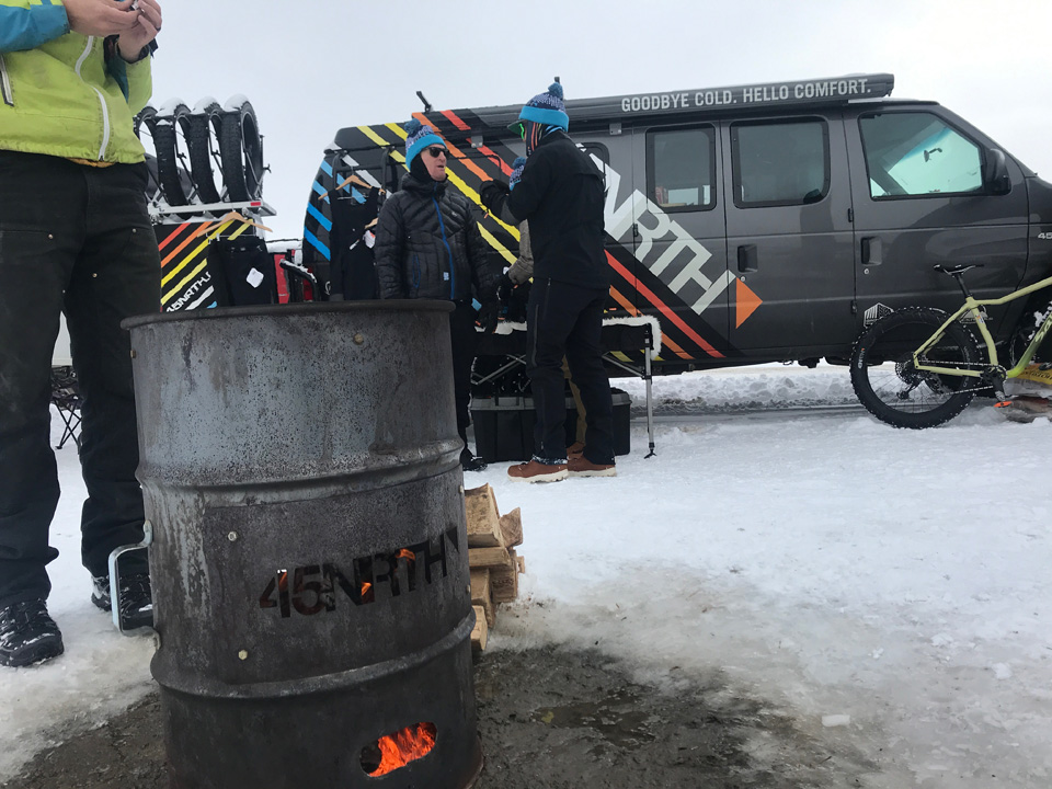 Rider warming his hands above a fire in a 55 gallon drum in front of the 45NRTH team van and equipment