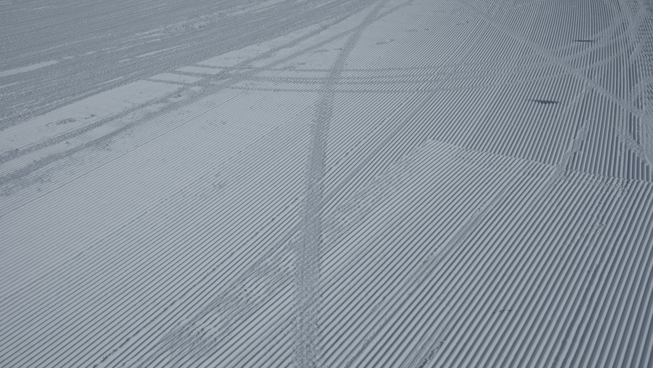 Freshly groomed snow with fat bike tire tracks