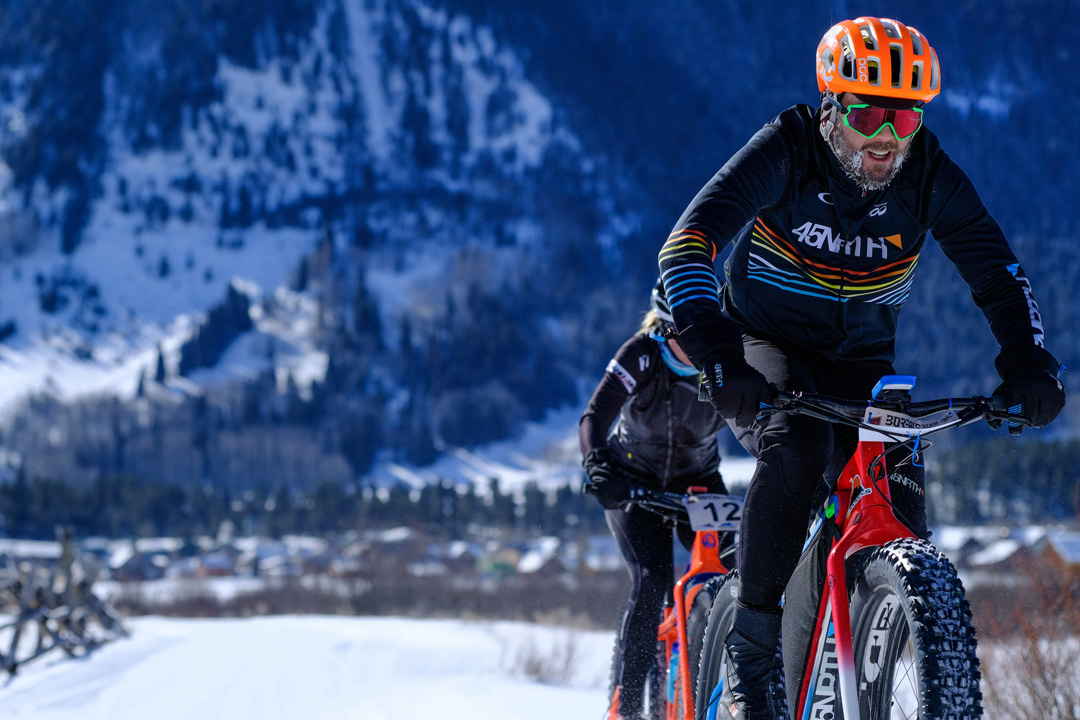 Two fat bike riders racing with mountains in the background