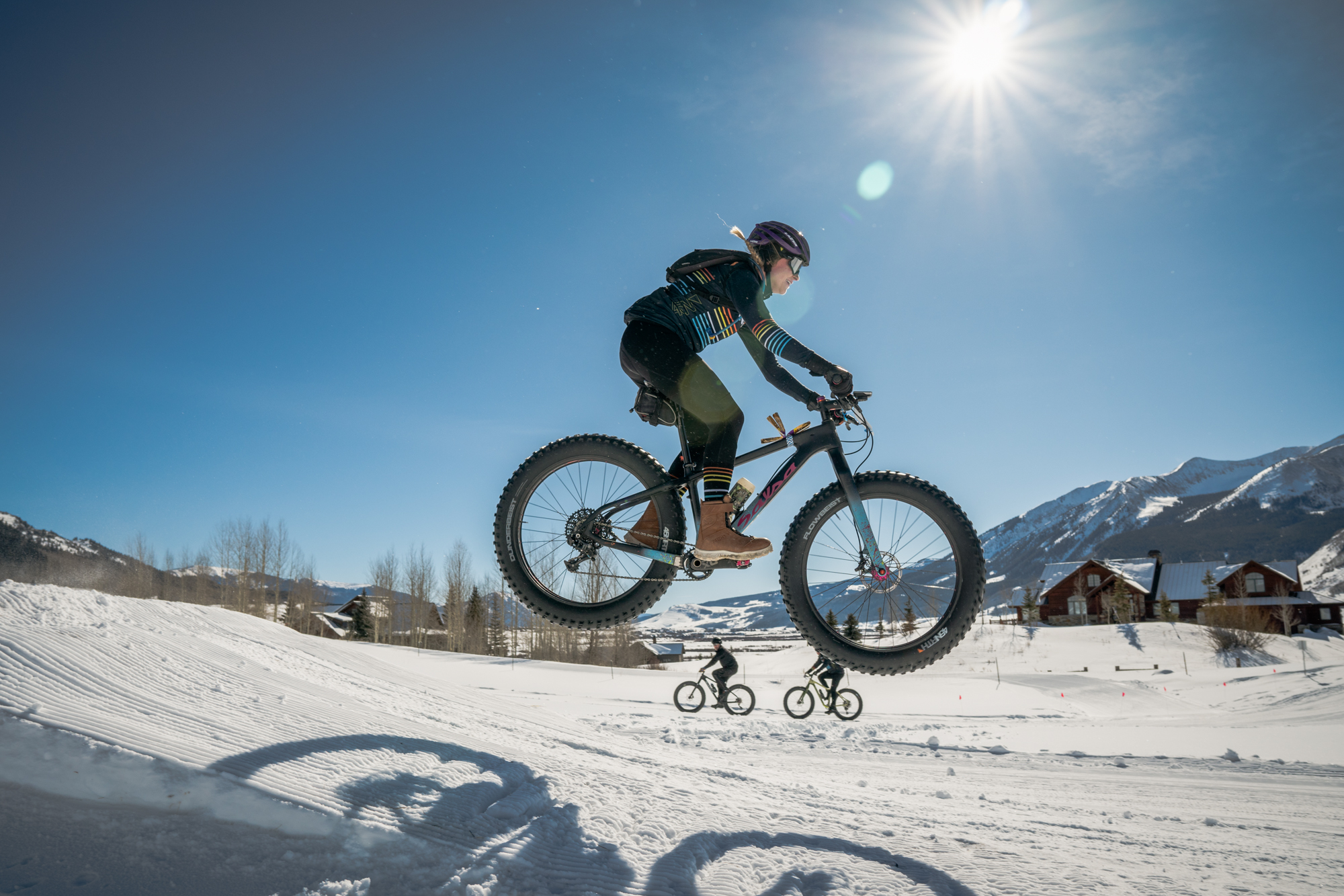 A person wearing a 45NRTH shirt gets airborne on their fat bike over a groomed trail