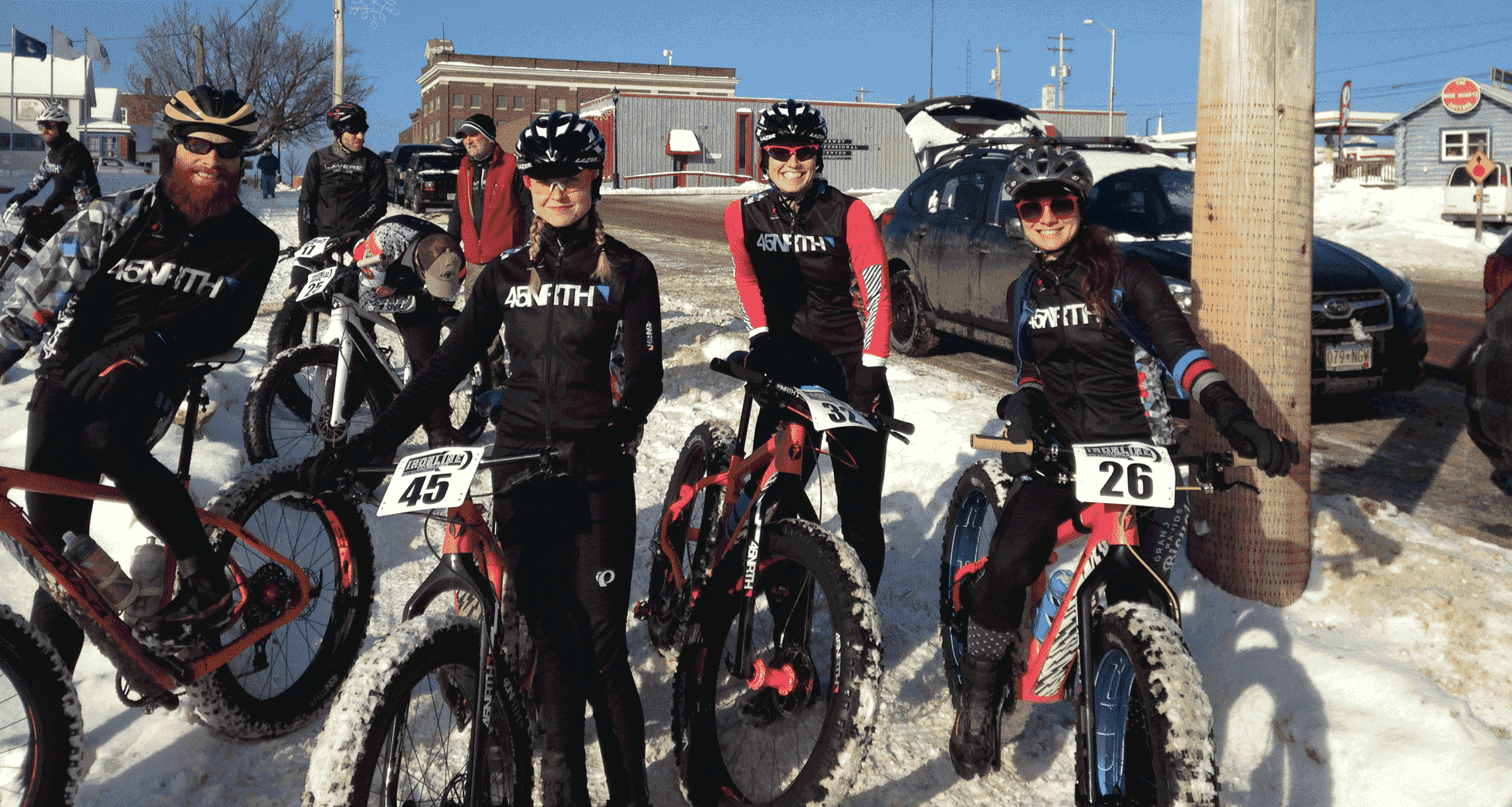 A group of four 45NRTH fat bike riders smiling and posing with their bikes