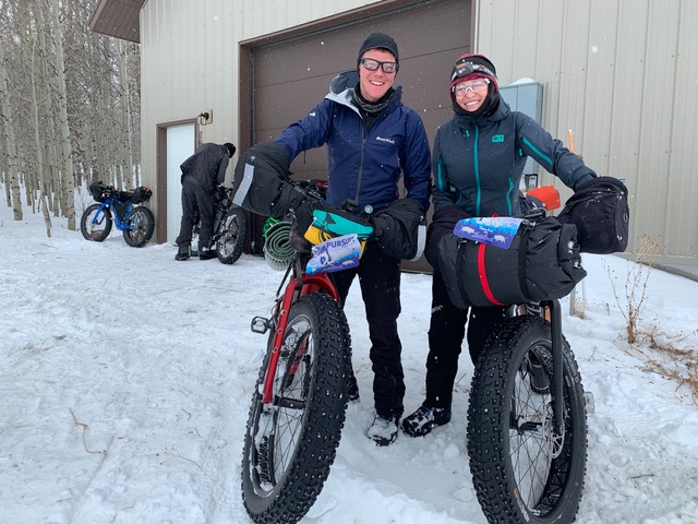 Two fat bike riders standing with their loaded bikes smiling in front of the Man Cave