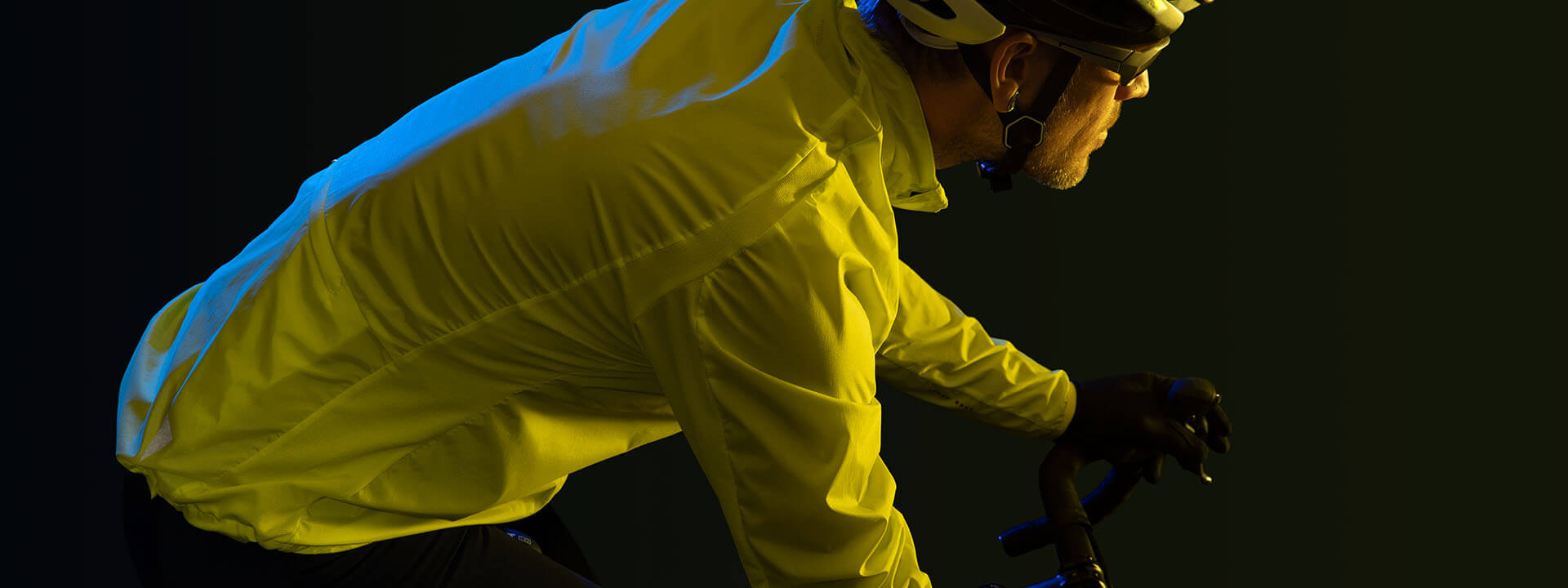 Male cyclist wearing bright yellow Torvald jacket