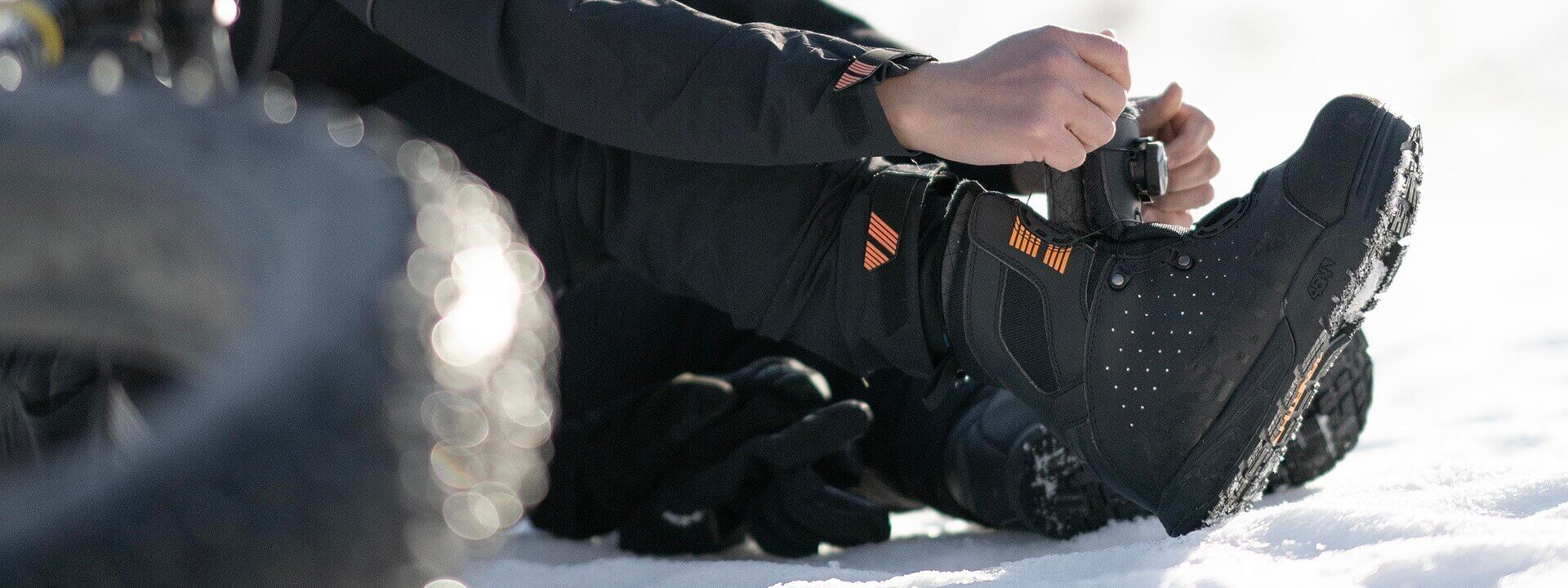 Cyclist sitting in snow putting on Wolvhammer Boa boot.