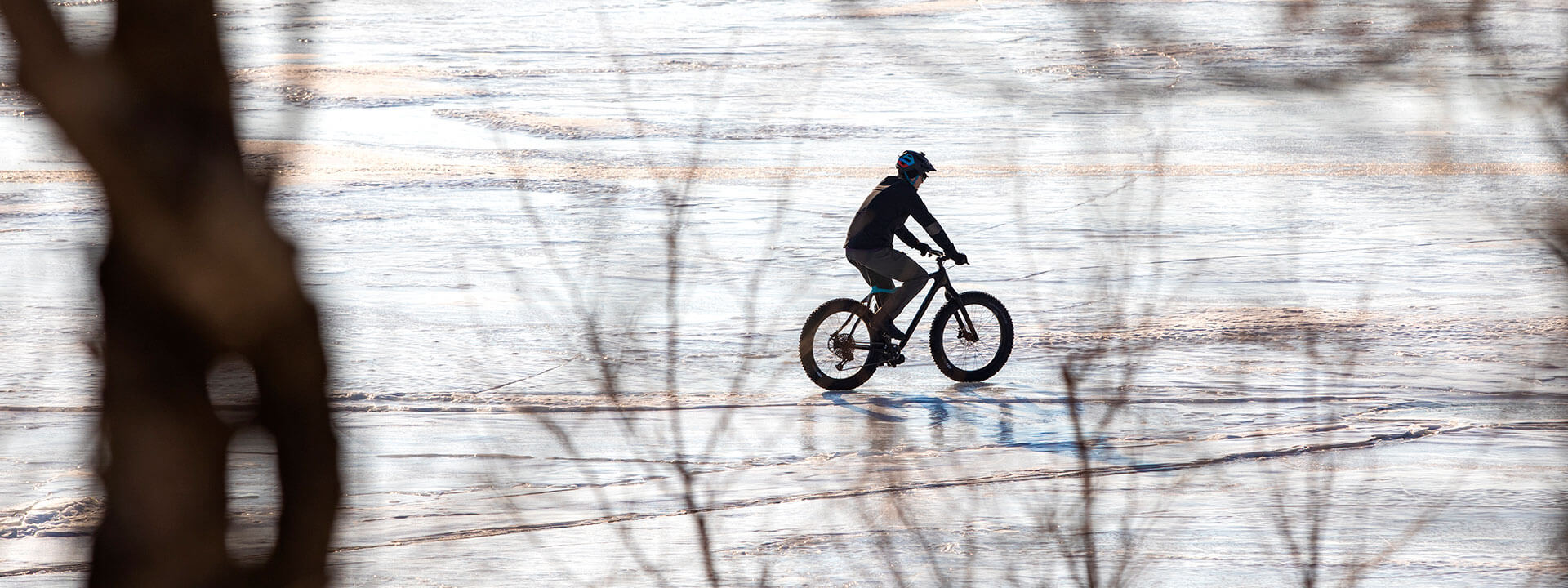 Cyclist on bike with studded tires riding across frozen lake.